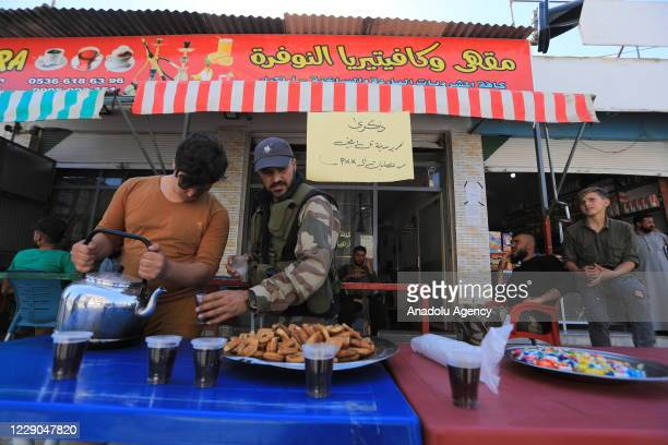 Members of Syrian National Army offer tea and cookies to people before an event to mark the first year of Operation Peace Spring as life turned to...