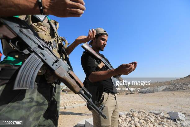 Members of Syrian National Army pray at the cemetery before an event to mark the first year of Operation Peace Spring as life turned to normal in Tal...