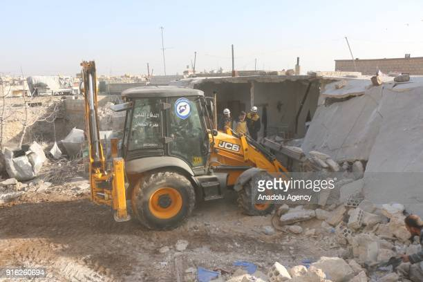 Members of Syrian NGOs conduct search and rescue operation amid debris after Assad Regime carried out an airstrike over Has village located at...