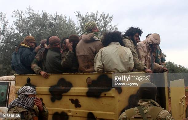 Members of Syrian opponents wait near a truck as Daesh militants get off after they were captured in Idlib Syria on February 13 2018 Syrian opponents...