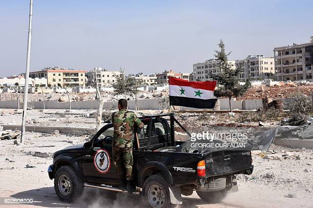 Members of Syrian progovernment forces drive their pickup in the village of Minyan west of Aleppo after they retook the area from rebel fighters on...