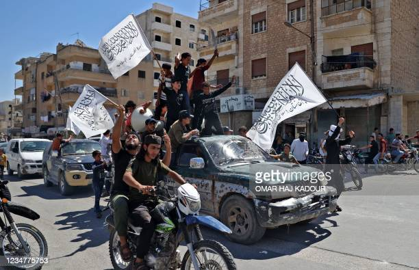 Members of Syria's top jihadist group the Hayat Tahrir al-Sham alliance, led by al-Qaeda's former Syria affiliate, parade with their flags and those...