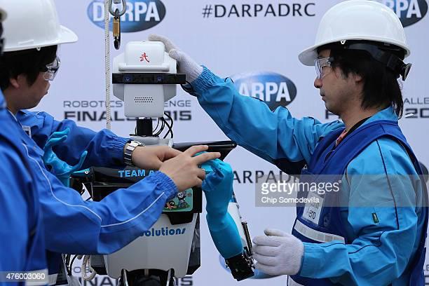 Members of Team Aero from the University of Tokyo prepare their robot in the 'Meet the Robots' area of th Defense Advanced Research Projects Agency...