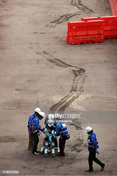 Members of Team Aero from the University of Tokyo right their robot after it fell over during its first run during the Defense Advanced Research...