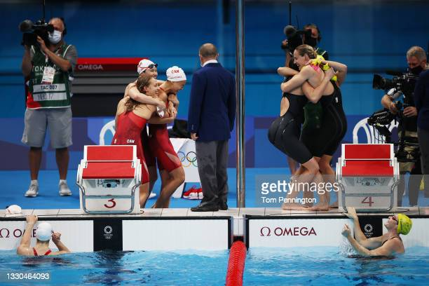 Members of Team Canada and Team Australia celebrate after competing in the Women's 4 x 100m Freestyle Relay Final on day two of the Tokyo 2020...