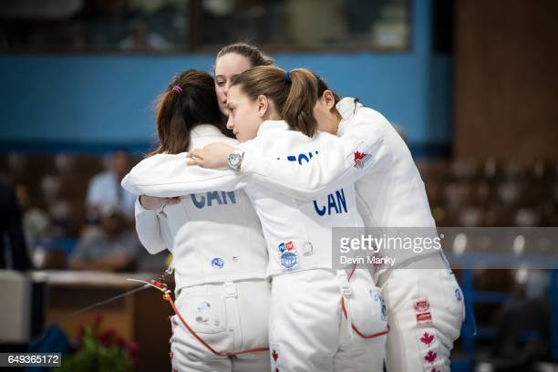 Members of Team Canada hug after a defeat to Team USA during competition in the gold medal match of the Junior Team Women's Epee competition at the...