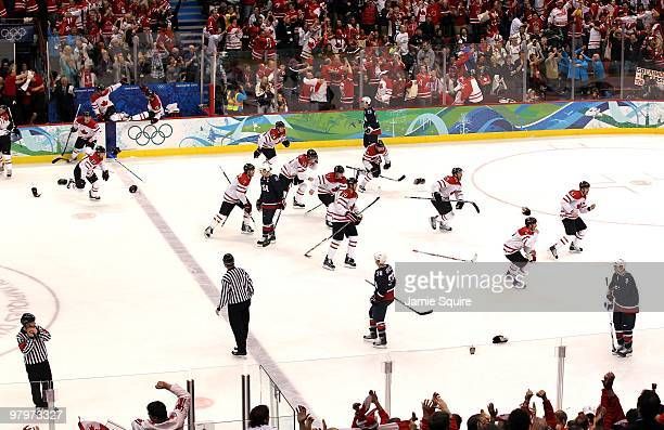 Members of Team Canada skate from the bench area toward teammate Sidney Crosby in the corner to celebrate their 32 overtime victory after the ice...