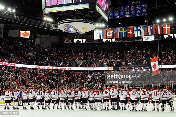Members of Team Canada stand at the blue line for the singing of the Canadian national anthem and the raising of the Canadian flag after defeating...