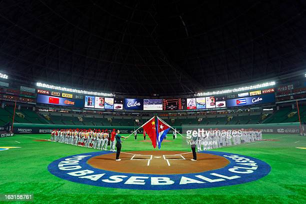 Members of Team Cuba and Team China are seen on the base paths during the playing of the national anthems before Pool A Game 4 between Team China and...