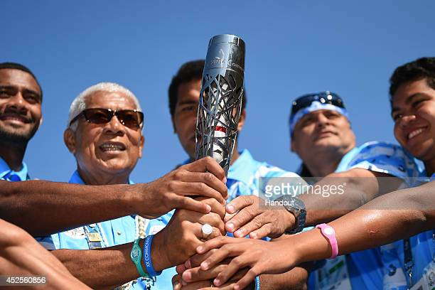 Members of Team Fiji hold the Glasgow 2014 Queen's Baton in the Team Fiji camp at the Commonwealth Games Athletes' Village on July 23 2014 in Glasgow...