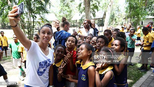 Members of team France take selfies with school children at the Port Moresby Nature Park on November 18 2016 in Port Moresby Papua New Guinea