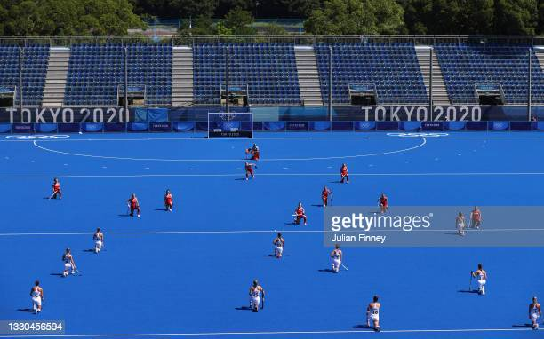 Members of Team Great Britain and Team Germany kneel against racism prior to the Women's Pool A match on day two of the Tokyo 2020 Olympic Games at...