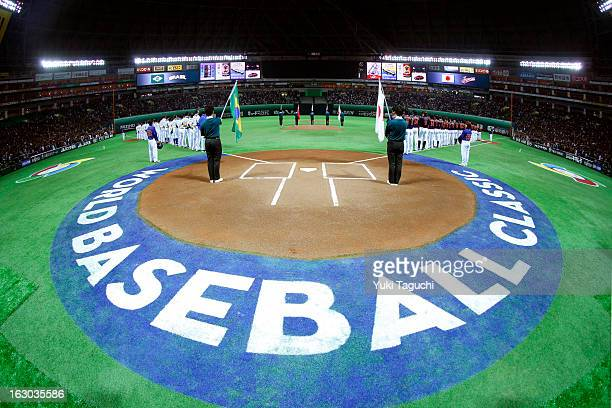 Members of Team Japan and Team Brazil are seen on the base paths during the national anthems before the Pool A Game 1 between Team Japan and Team...