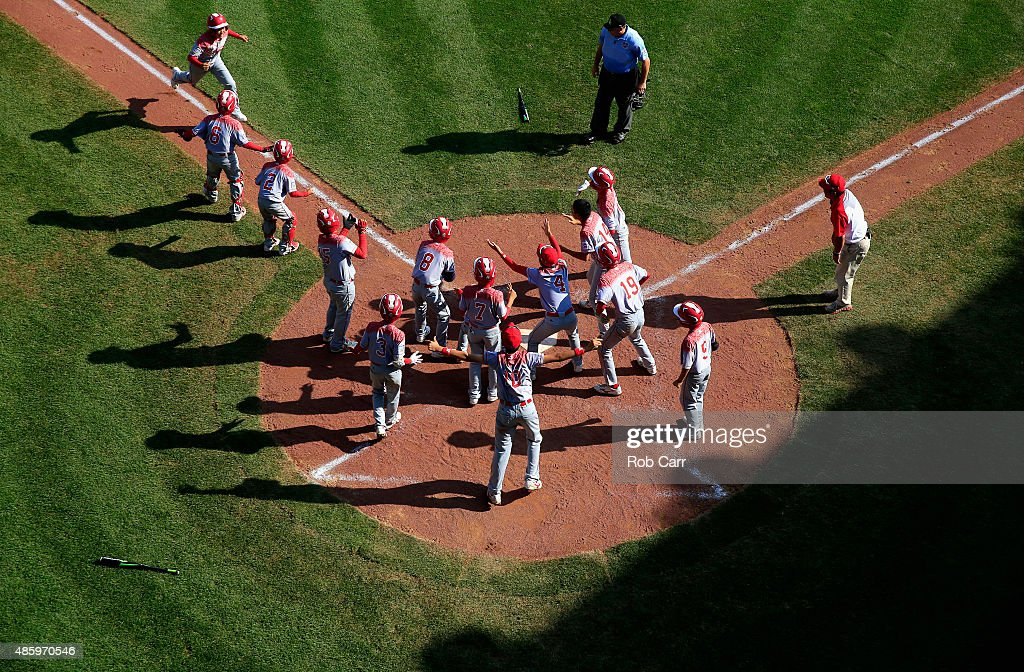 Members of team Japan celebrate while waiting for Masafuji Nishijima #16 to cross the plate after hitting a three RBI home run against the Mid-Atlantic team from Red Land Little League of Lewisberry, Pennsylvania during the third inning of the Little League World Series Championship game at Lamade Stadium on August 30, 2015 in South Willamsport, Pennsylvania.