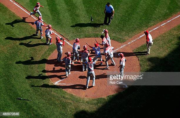 Members of team Japan celebrate while waiting for Masafuji Nishijima to cross the plate after hitting a three RBI home run against the MidAtlantic...