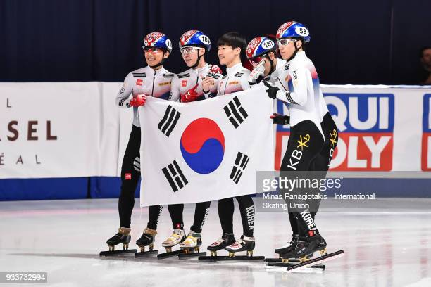 Members of team Korea hold up the Republic of Korea's flag after placing first in the men's 5000 meter relay Final during the World Short Track Speed...