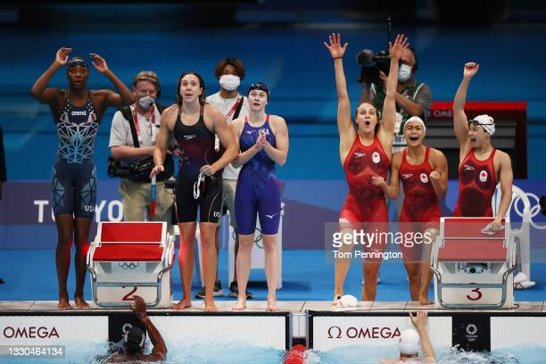 Members of Team United States and Team Canada react while competing in the Women's 4 x 100m Freestyle Relay Final on day two of the Tokyo 2020...