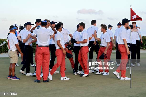 Members of Team USA and Team Great Britain and Ireland shake hands on the 18th green after Team USA beat Team Great Britain and Ireland 14-12 during...