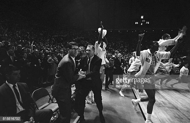 Members of Texas Western rush onto the court as the final gun sounded giving them a 72-65 win over the Kentucky Wildcats and the NCAA basketball...