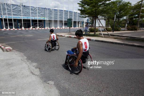 Members of Thailand's national wheelchair basketball team head back to their quarters after a training session at a government sports facility in...
