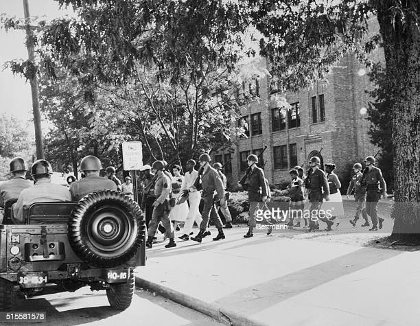 Members of the 101st Airborne escort black students away from a quiet Central High School at the end of the day