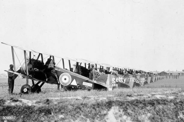 Members of the 148th US Aero Squadron clambering into their planes lined up on an airfield.