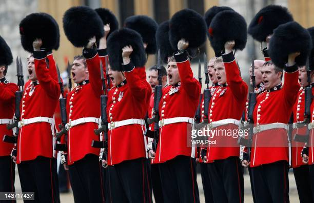 Members of the 1st Battalion and No. 7 Company the Coldstream Guards raise their bearskins as they give three cheers for Queen Elizabeth II after...