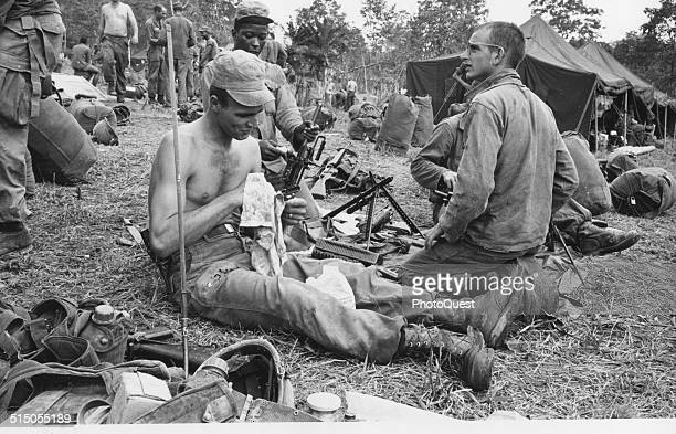 Members of the 1st Cavalry clean weapons after a fiveday battle near Saigon Vietnam October 19 1965