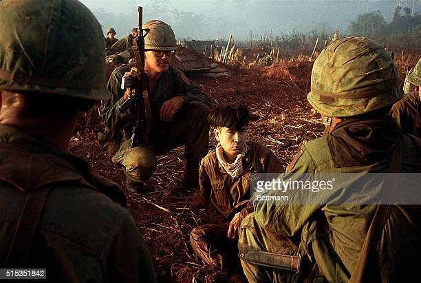 Members of the 1st Infantry Division watch over a young Vietcong prisoner of war captured during Operation Quicksilver | Location Near Bu Dop South...