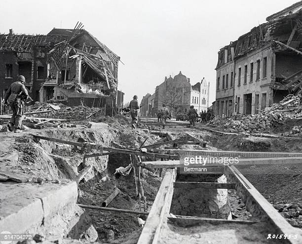 Members of the 2nd Armored Division US 9th army move through the shattered town of Krefeld Germany Co D 41st Regiment