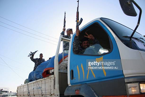 Members of the 2nd Iraqi police regiment raise their weapons celebrating their return to the southern Iraqi city of Basra on April 14 2015 after...