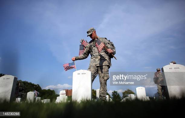 Members of the 3rd US Infantry Regiment place American flags at the graves of US soldiers buried in Section 60 at Arlington National Cemetery in...