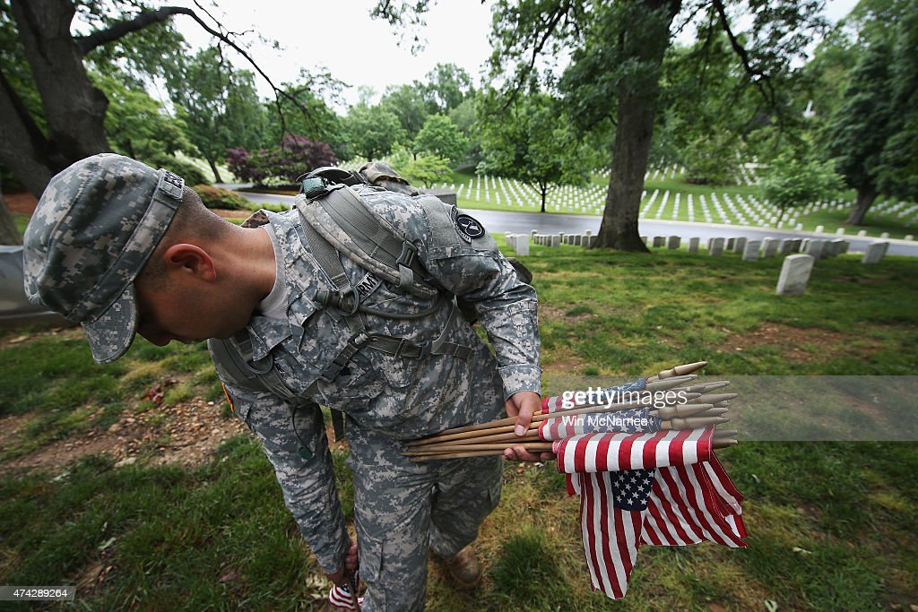 Members of the 3rd U.S. Infantry Regiment place American flags at the graves of U.S. soldiers buried at Arlington National Cemetery, in preparation for Memorial Day May 21, 2015 in Arlington, Virginia. 'Flags-In' has become an annual ceremony since the 3rd U.S. Infantry Regiment (The Old Guard) was designated to be an Army's official ceremonial unit in 1948.