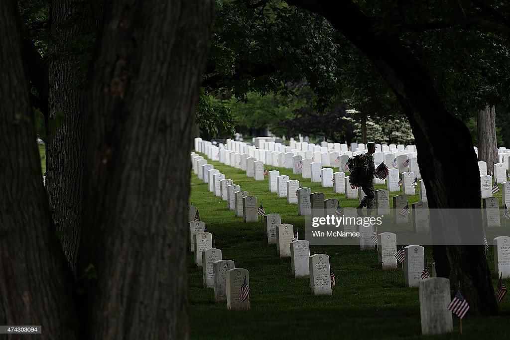 Members of the 3rd U.S. Infantry Regiment place American flags at the graves of U.S. soldiers buried at Arlington National Cemetery, in preparation for Memorial Day May 21, 2015 in Arlington, Virginia. 'Flags-In' has become an annual ceremony since the 3rd U.S. Infantry Regiment (The Old Guard) was designated to be an Army's official ceremonial unit in 1948