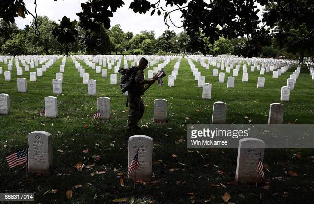 Members of the 3rd U.S. Infantry Regiment place flags at the headstones of U.S. Military personnel buried at Arlington National Cemetery, in...
