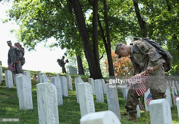 Members of the 3rd US Infantry Regiment 'The Old Guard' place flags at grave sites during the 'FlagsIn' ceremony May 26 2016 at Arlington National...