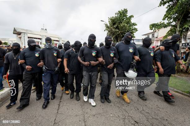 Members of The 500 Brothers group alongside other demonstrators take part in a march in support of the general strike in Cayenne on the French...