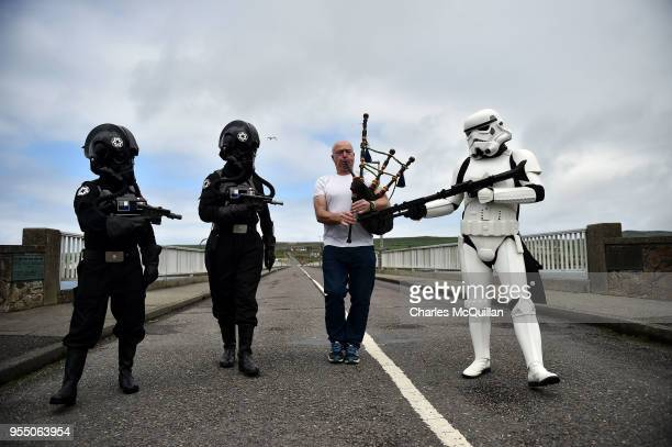 Members of the 501st Irish Legion dressed as a stormtrooper and pilot troopers from Star Wars 'arrest' a man playing bagpipes on May 5 2018 in...