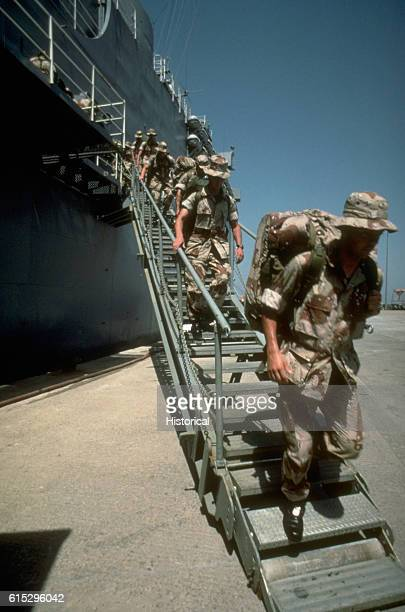 Members of the 6th Marine Regiment disembark from the amphibious transport dock USS Dubuque upon their arrival in Saudi Arabia as part of Operation...