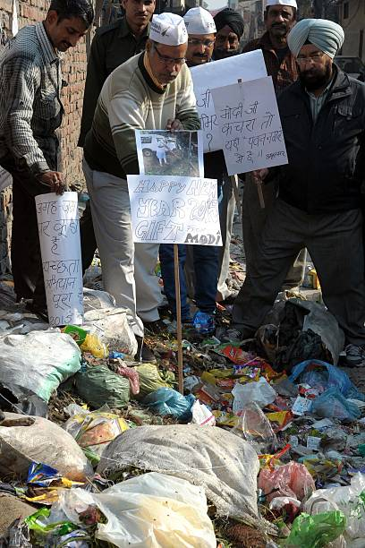 Members of the Aam Aadmi Party place placards on a garbage heap during a demonstration in Amritsar on January 2 2015 The demonstrators were...