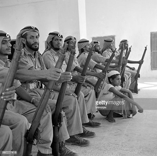 Members of the Abu Dhabi defence force pose for the camera with a young boy in the grounds of the Royal Palace July 1965