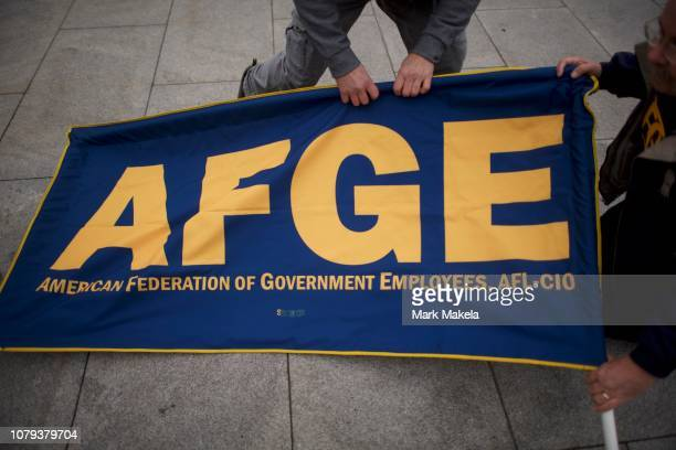 Members of the AFGE set up a banner before joining furloughed federal workers and area elected officials during a protest rally in front of...