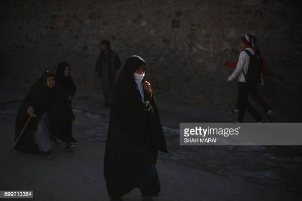 Members of the Afghan Hazara community walk near the site of blasts at a Shiite cultural centre in Kabul on December 28 2017 At least 40 people were...