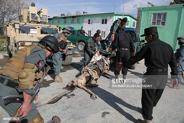 Members of the Afghan National Police drag the body of an alleged militant after fighting between Taliban and Afghan security forces in Mula Khil...