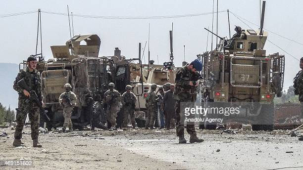Members of the Afghan security forces inspect the site of a suicide bomb attack targeting a convoy of US forces near Nangarhar airport which is used...