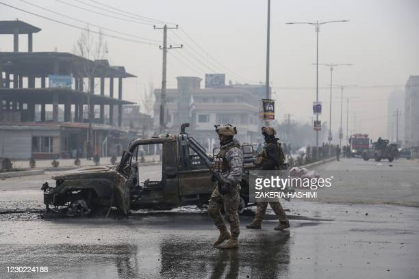 Members of the Afghan security forces stand at the site of an attack, in Kabul on December 20, 2020. - A car bomb killed eight people and wounded...