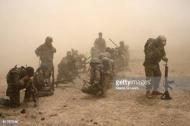 Members of the Afghan Security Forces wait to be extracted by helicopter after an operation to search three compounds and look for weapons on July 1...