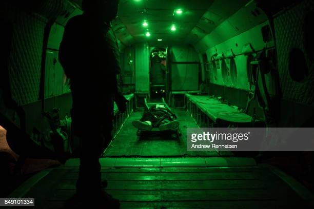Members of the Afghan Special Forces load a casualty on a helicopter during a casevac night training of Afghanistan Special Forces by the United...