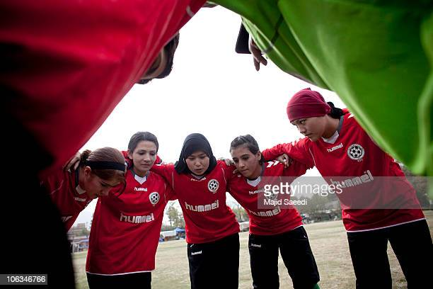 Members of the Afghan women's national football team huddles during a match with the NATO-led International Security Assistance Force women's team in...