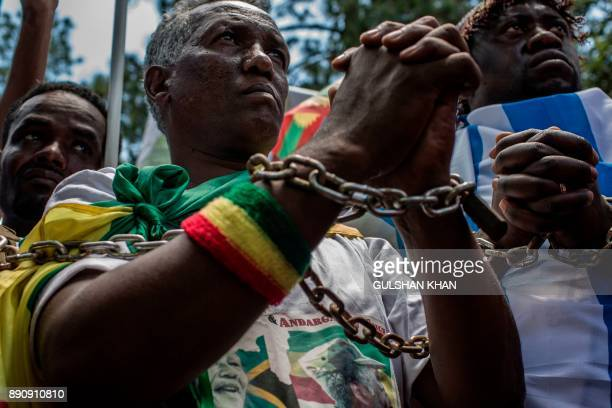 Members of the Africa Diaspora Forum civil society organisations churches trade unions and other coalitions wear chains and shout slogans during a...